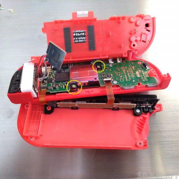 Nintendo Switch の Joy-Con(右) を開けてバッテリーが乗っている仕切りを持ち上げると右スティックが見えるので、固定しているネジを外す。